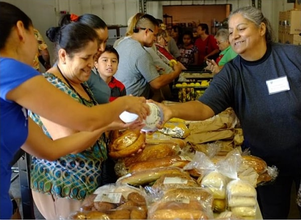 community-food-bank-Maria-Elena-handing-out-bread