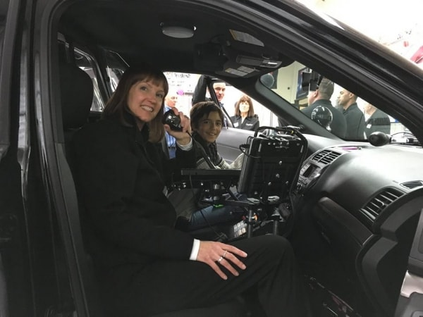 Food Bank CEO Maria Thomas in police vehicle at Chamber of Commerce mixer in Hollister, CA