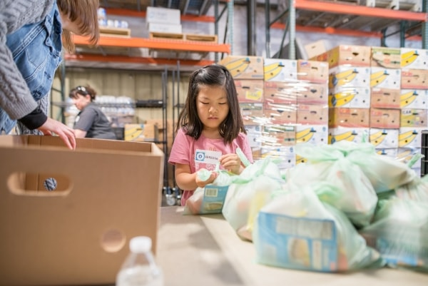 Child helps volunteers pack backpack fill bags at food bank of San Benito County